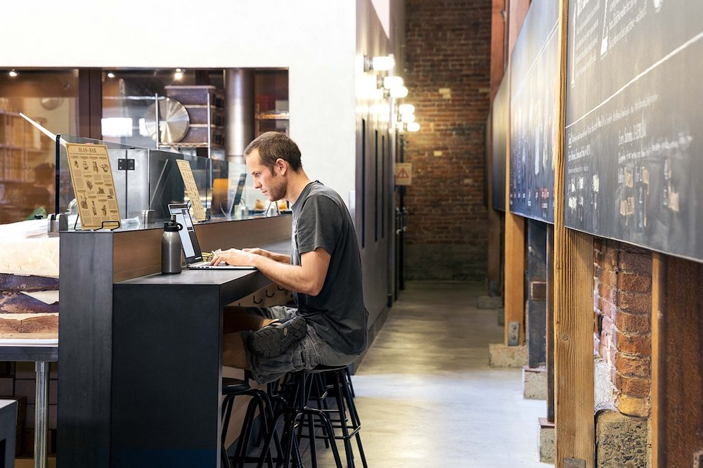 man working on laptop at wooden desk