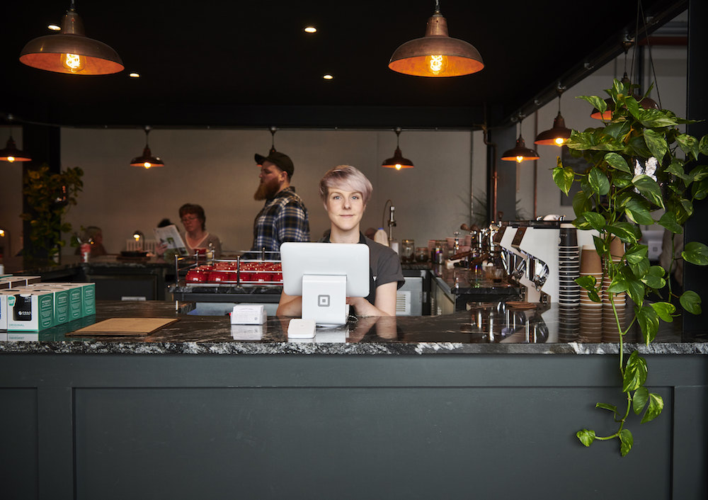 barista behind bar with Square Stand