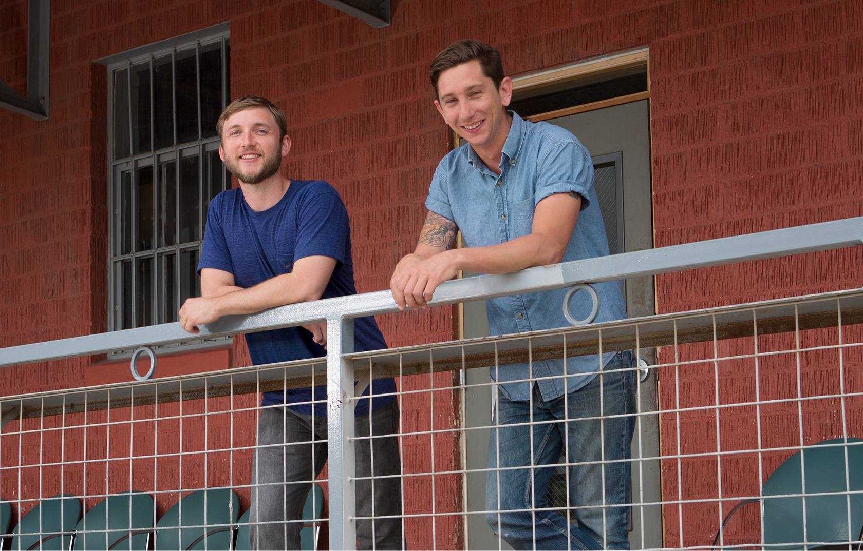 Two men smiling and leaning on a railing