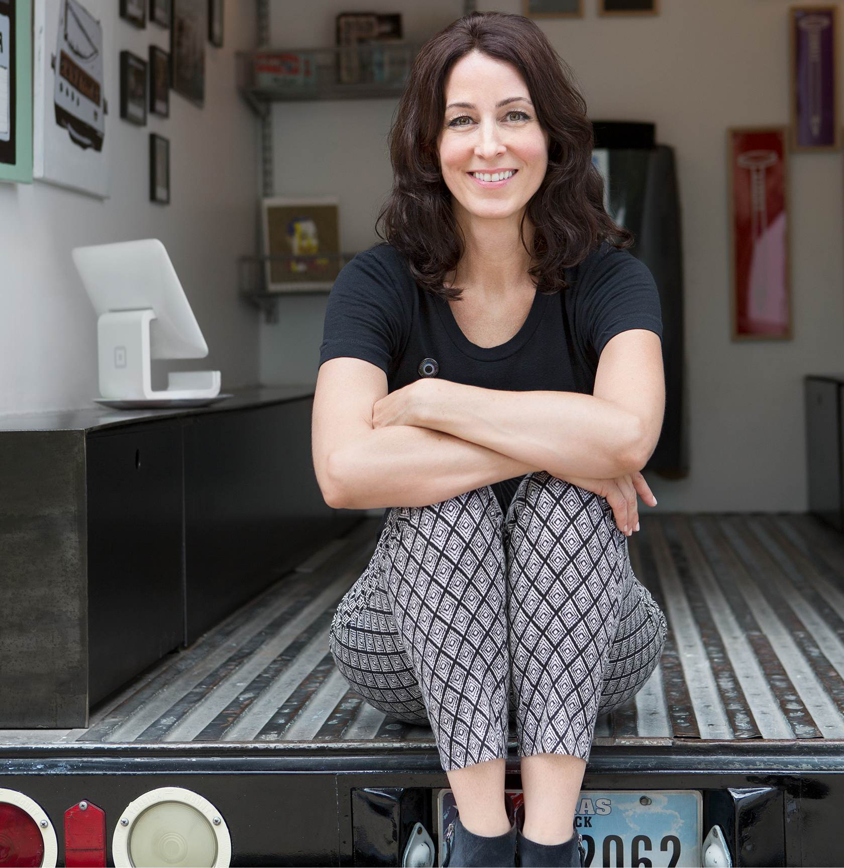 Photo of a woman sitting in the back of a mobile art gallery truck with a Square Stand in the background