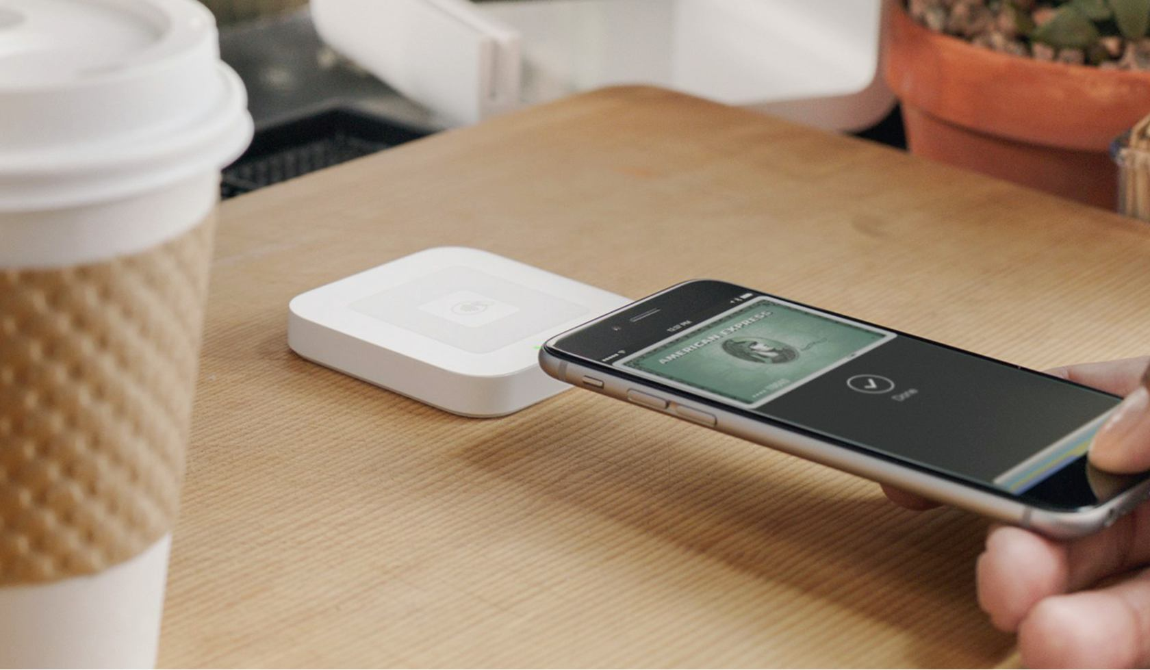 Photo of a phone making an Apple Pay payment near a Square Reader on a countertop