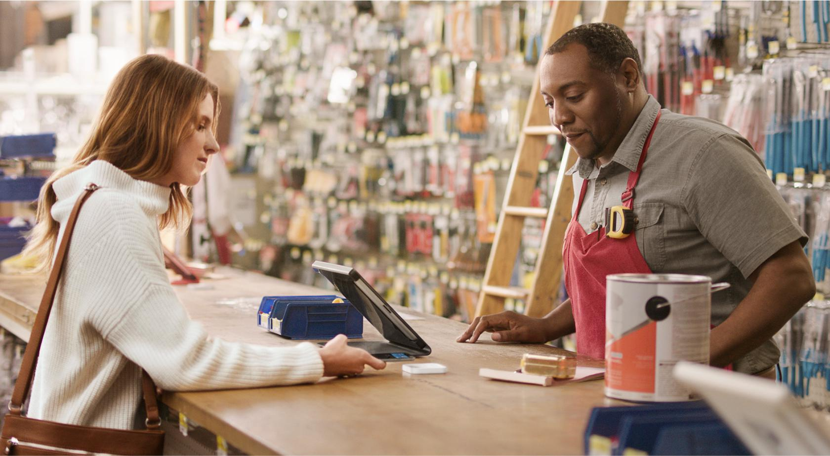 A woman paying with a phone using Apple Pay at the counter of a hardware store