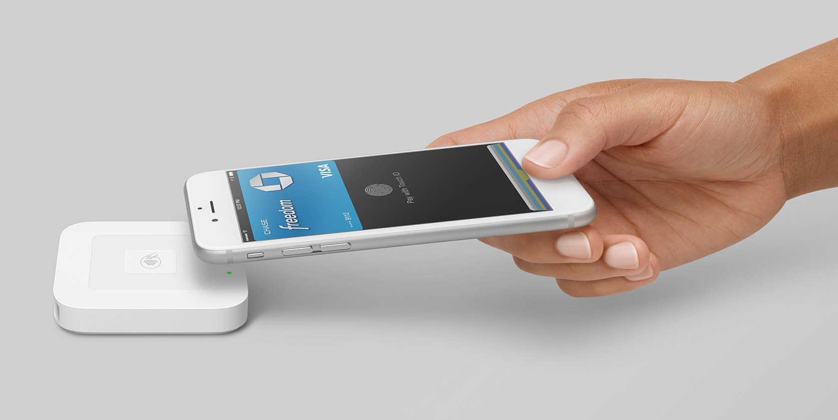 Image of hand holding iPhone paying with Apple Pay near Square contactless and chip reader