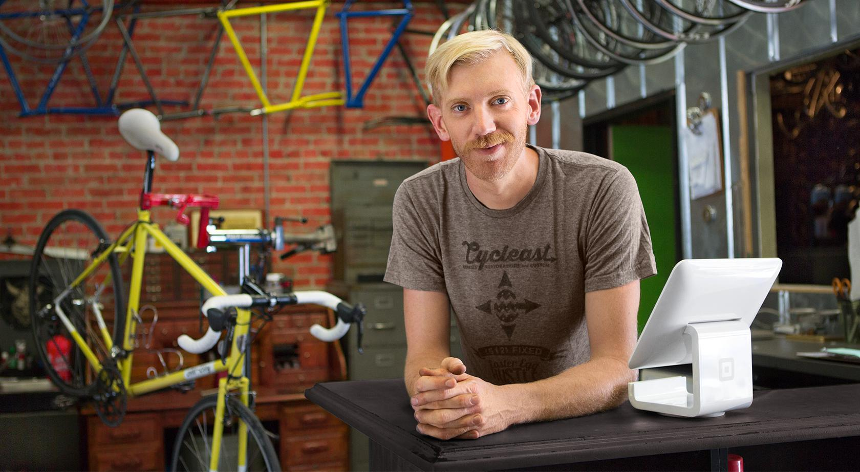 Man standing behind the counter of a bicycle repair shop