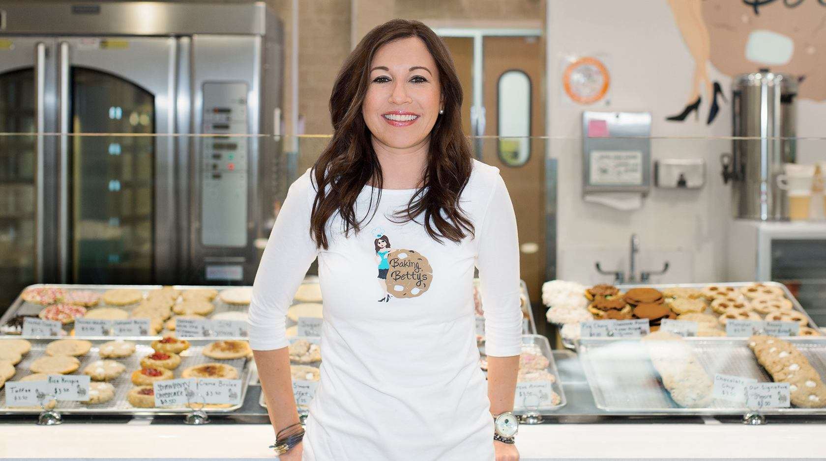 Woman standing in front of a case of pastries in a bakery